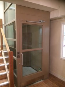Extremely Compact Platform Lift in corner by stairs